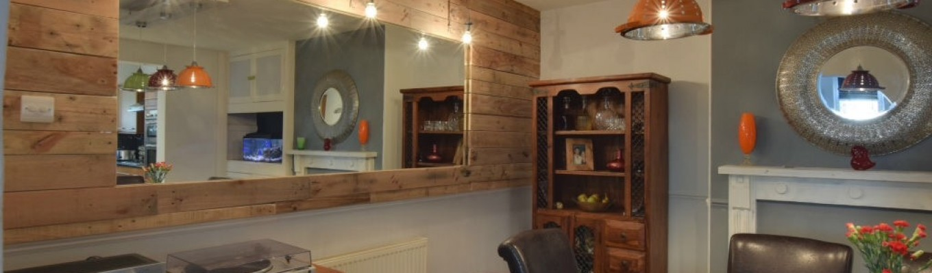 Dining Room make-over.  Budget £2000. Used existing furniture.  Walls in soft grey and antique white.  Reclaimed pallet wood wall cladding and reclaimed wardrobe mirror. Shabby chic fireplace surround.